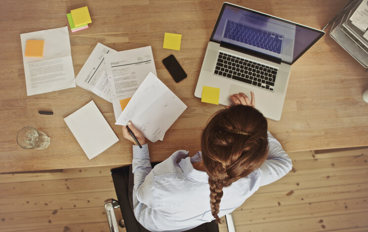 Businesswoman working at her office desk with documents and laptop - Blogpost - 5 tips for navigating bad days as an entrepreneur