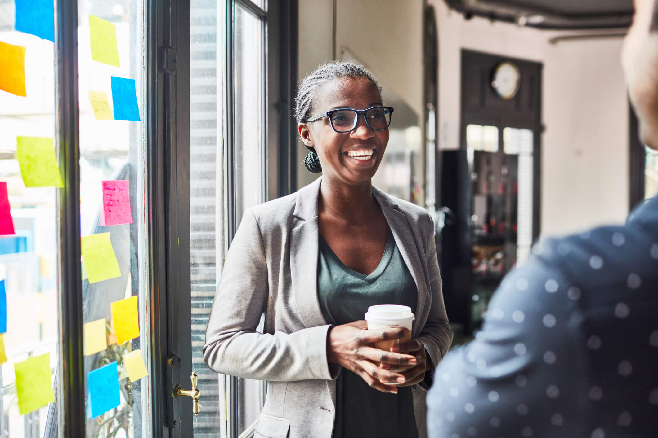 Smiling young woman talking with her colleague while having coffee at office. Business people having a casual talk during coffee break.